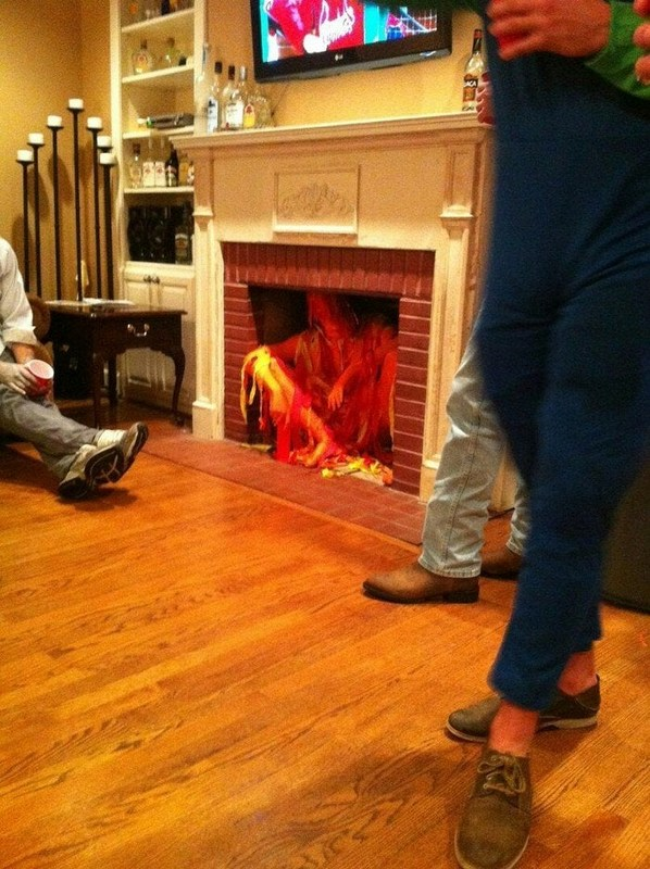 Man dressed as a fire sitting in a fireplace